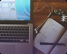 Mesa com notebook, fone e caderno
